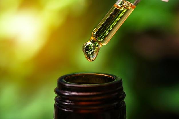 Olio di canapa cbd mano che tiene la gocciolina di olio di cannabis su sfondo nero
