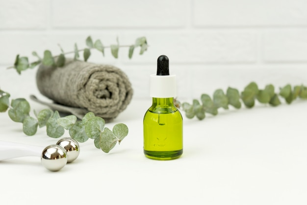 L'olio di cbd per il massaggio del viso e il rullo per il viso si trovano su un tavolo bianco