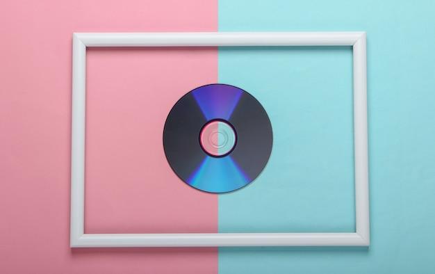 Disco cd in cornice bianca su superficie pastello rosa blu