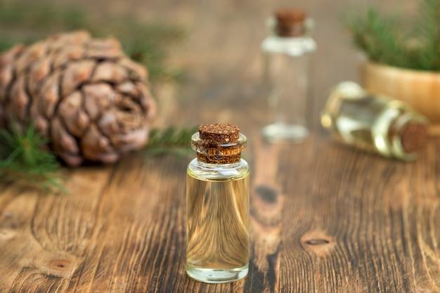 Olio essenziale di cedro in una bottiglia di vetro. focalizzazione morbida. fondo in legno