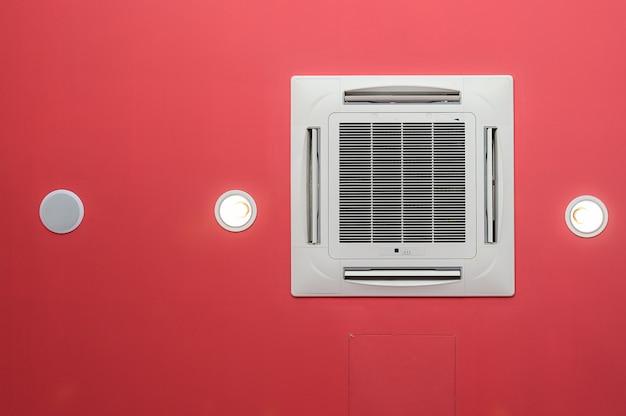 Condizionatore d'aria a soffitto su plafoniera rossa e altoparlante.