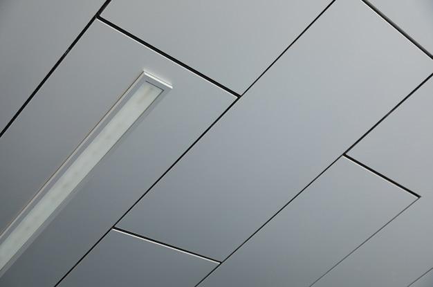 Soffitto coperto con pannelli bianchi lisci con una lampada