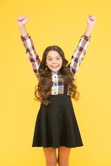 Festeggia l'infanzia. ragazza felice con sfondo giallo mani alzate. piccola ragazza torna a scuola. ragazza che celebra le vacanze scolastiche. ragazza carina con un sorriso di capelli lunghi in abbigliamento formale.