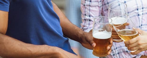 Celebrare. mani di amici, colleghi mentre bevono birra, si divertono, tintinnano bottiglie, bicchieri insieme.