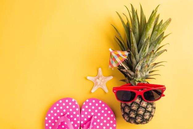 Celebrate summer pineapple day concept vista dall'alto piatto laici di divertente ananas fresco in occhiali da sole con stelle marine e pantofola