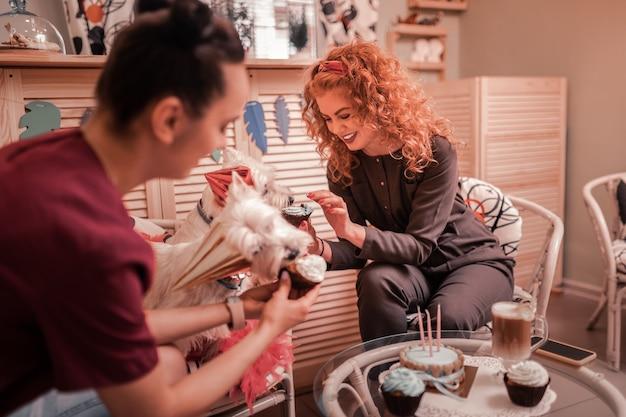 Festeggiare il compleanno. due donne festeggiano il compleanno dei loro cani con cupcakes e cappuccino