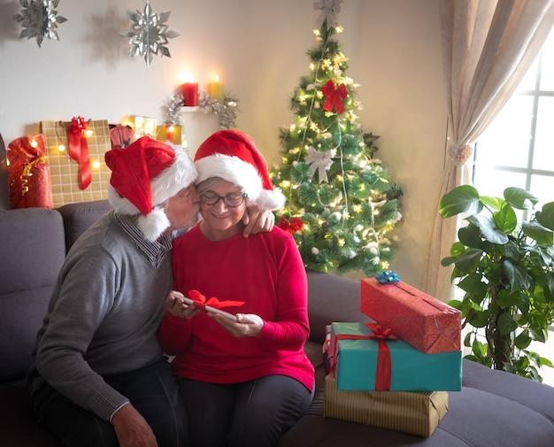 Festeggiamo il natale insieme con un bacio. una bella coppia di anziani che si gode lo scambio di doni. indossano i cappelli di babbo natale. bellissimo albero di natale sullo sfondo e regali per la famiglia