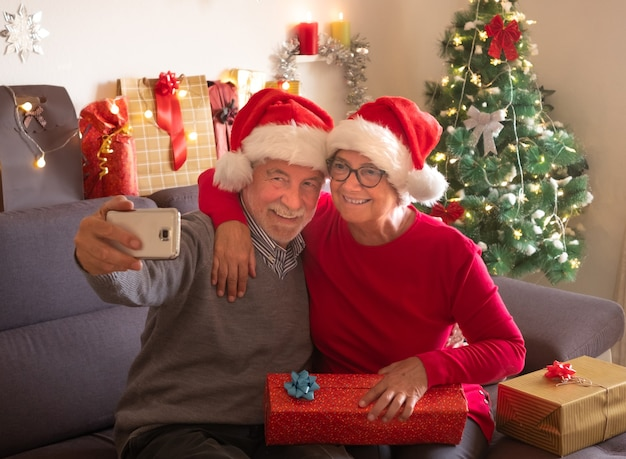 Festeggiamo il natale insieme con un selfie. una bella coppia di anziani che si gode lo scambio di doni. indossano i cappelli di babbo natale. bellissimo albero di natale sullo sfondo e regali per la famiglia