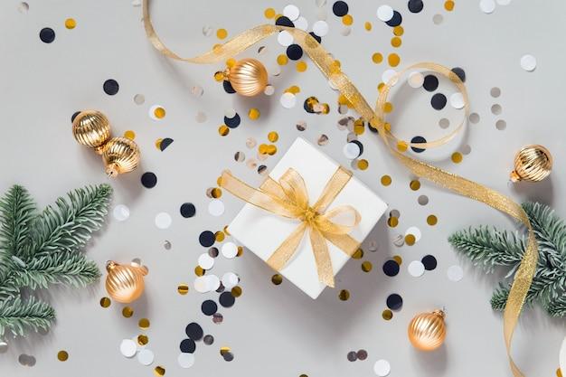 Celebrando la disposizione piatta con decorazioni di capodanno, palline dorate, coriandoli e rami dell'albero di natale