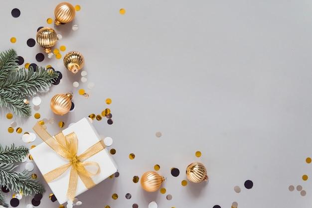 Celebrando la disposizione piatta con decorazioni di capodanno palline dorate coriandoli presenti sfondo grigio