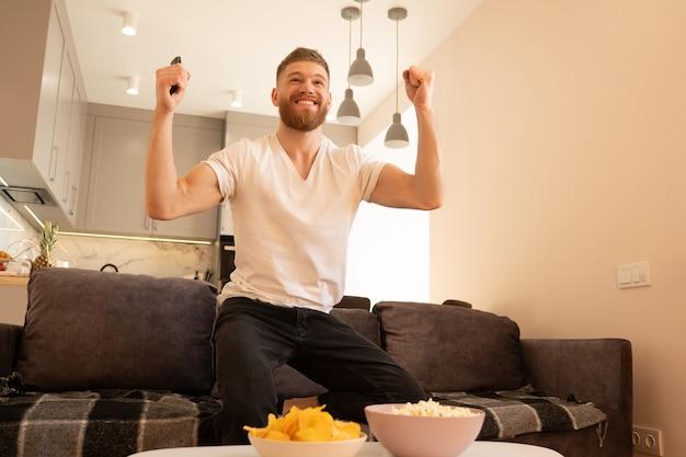 Celebrando l'uomo, siediti sul divano e guarda la tv o un film. giovane ragazzo barbuto europeo che tiene il telecomando. ciotole con patatine e popcorn sul tavolo. concetto di riposo a casa. interno del monolocale