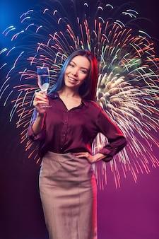 Celebrando il colpo verticale di capodanno di una giovane donna asiatica felice con un bicchiere di