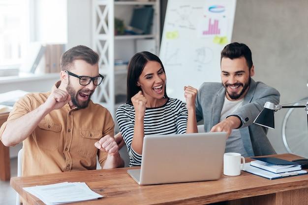 Celebrando il successo. tre uomini d'affari felici in abbigliamento casual intelligente guardando il laptop e gesticolando