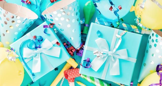 Sfondo di celebrazione con scatola regalo, stelle filanti colorate, coriandoli e cappelli da festa di compleanno vista dall'alto