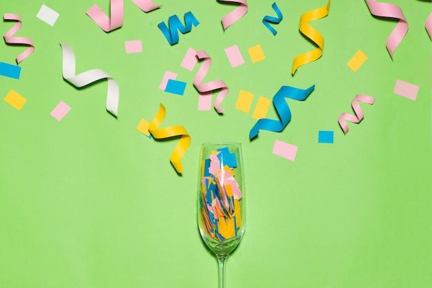 Celebrazione piatta con articoli per feste colorati su sfondo verde.