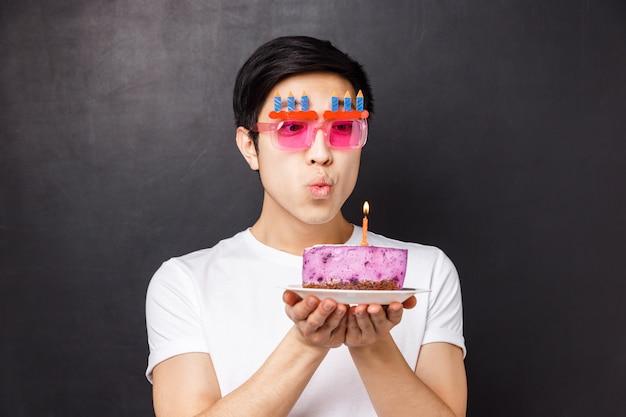 Concetto di celebrazione, vacanze e compleanno. ritratto del primo piano dell'uomo asiatico sveglio vago in vetri divertenti del partito, spegnendo candela per esprimere desiderio, sognando il b-day, supporto