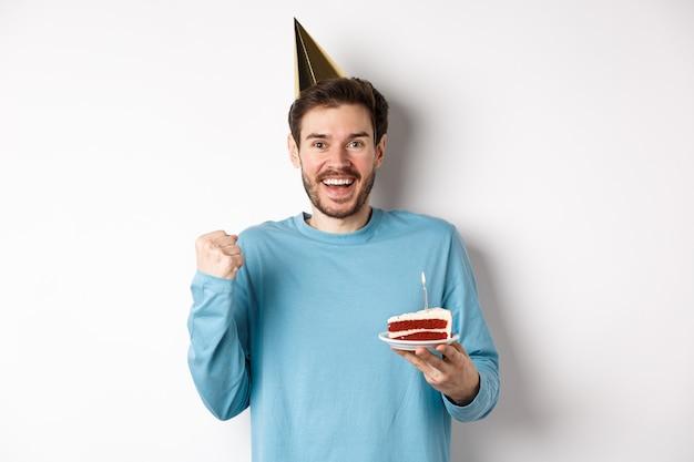 Celebrazione e concetto di vacanze. giovane allegro che festeggia il compleanno in cappello da festa, dicendo sì e pompa a pugno con gioia, tenendo in mano una torta di compleanno, sfondo bianco.