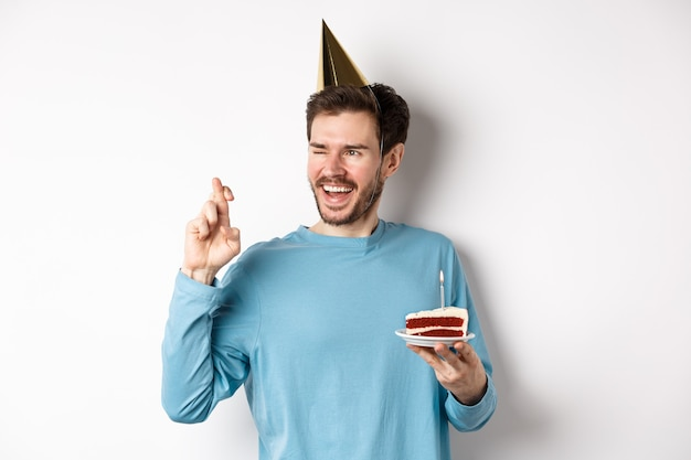 Celebrazione e concetto di vacanze. giovane allegro che esprime desiderio per il compleanno, tenendo le dita incrociate e indossando il cappello del partito, in piedi con la torta di compleanno, sfondo bianco.