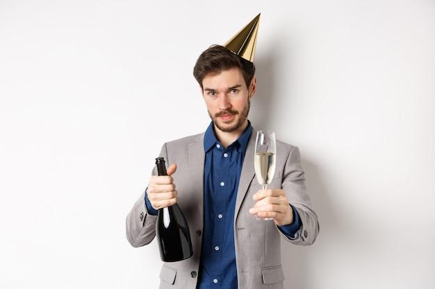 Celebrazione e concetto di vacanze. uomo bello in vestito e cappello di compleanno che dà un bicchiere di champagne
