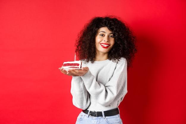 Celebrazione e concetto di vacanze. bella donna sorridente che celebra il compleanno, che tiene la torta di b-day con la candela e che esprime il desiderio, in piedi felice su fondo rosso.