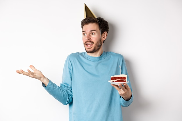 Celebrazione e concetto di vacanze. uomo sorpreso che scrolla le spalle incredulo, distogliendo lo sguardo, tenendo la torta di compleanno e indossando il cappello a cono del partito, sfondo bianco.