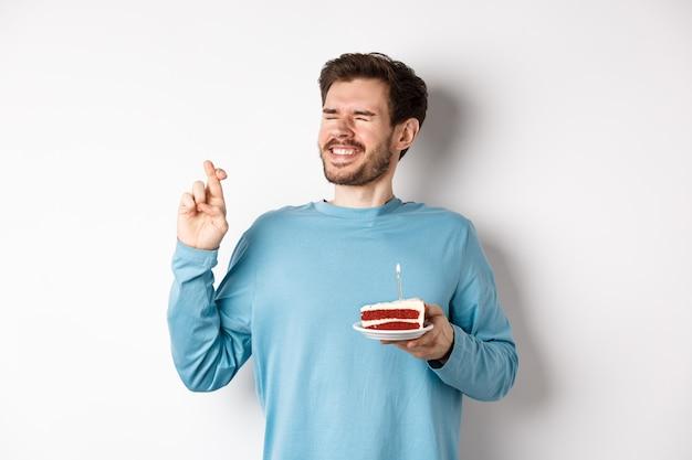 Celebrazione e concetto di vacanze. giovane uomo festeggia il compleanno, incrociare le dita per buona fortuna, esprimendo un desiderio sulla torta di compleanno con candela accesa, in piedi su sfondo bianco.