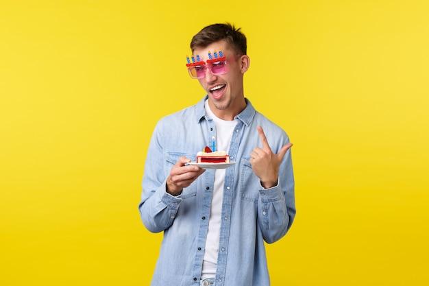 Celebrazione, vacanze e concetto di emozioni della gente. ragazzo allegro di buon compleanno in occhiali da sole da festa, festeggia con gli amici, sorride gioioso e tiene in mano una torta di compleanno, in piedi su sfondo giallo.