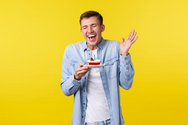 Celebrazione, vacanze e concetto di emozioni della gente. ragazzo felice gioioso e sorpreso che celebra il b-day alla festa. ridendo e sorridendo di gioia, tenendo piatto con torta di compleanno, sfondo giallo.