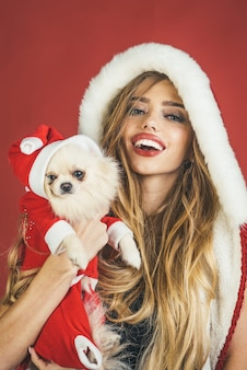 Celebrazione e concetto di umore del nuovo anno natale donna felice con cucciolo vacanze invernali cane anno nuovo