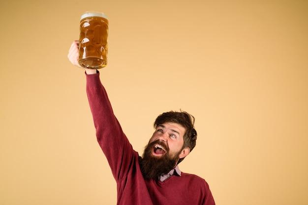 Celebrazione del festival dell'oktoberfest uomo barbuto con un bicchiere di birra chiara che tosta l'uomo tiene una tazza di