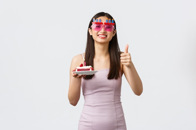 Celebrazione, festa e concetto di vacanze. donna asiatica sorridente gioiosa in occhiali e vestito, mostra il pollice in su, festeggia il proprio compleanno