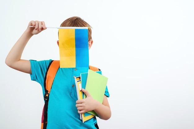 Celebrazione vacanze ucraine. bambino che tiene bandiera ucraina. persone, istruzione, apprendimento e concetto di scuola.