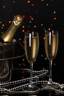 Champagne celebrativo con calici su sfondo di luci di natale