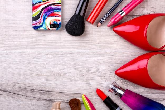 Cellulare, cosmetici e scarpe. telefono vicino al trucco. la moda aiuta ad esprimere la bellezza. parte inalienabile della vita moderna.