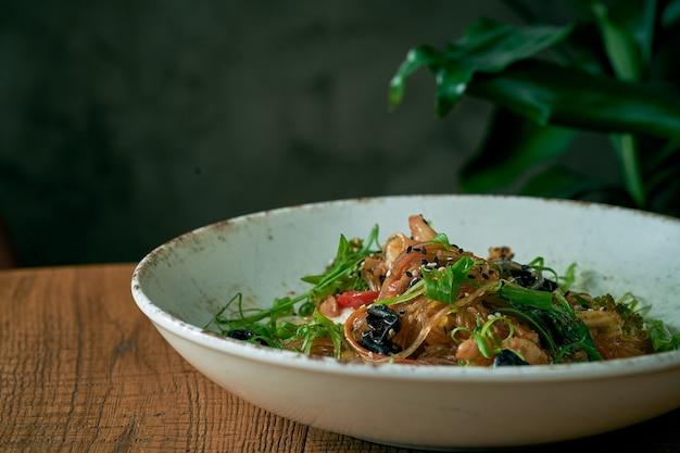 Tagliatelle di cellophane con gamberi e verdure, funghi shiitake in un piatto bianco. wok di spaghetti di riso