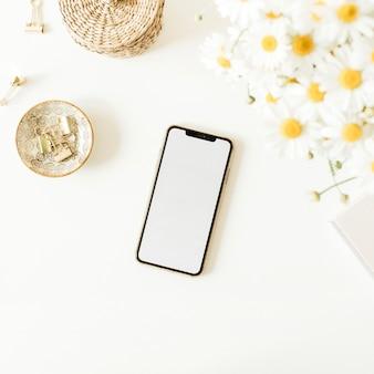 Cellulare con lo spazio vuoto della copia del modello sul tavolo con il mazzo dei fiori della margherita della camomilla su fondo bianco
