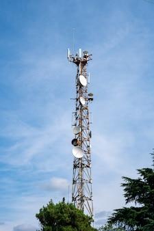 Antenna cellulare su uno sfondo di cielo blu con tempo soleggiato. comunicazione.
