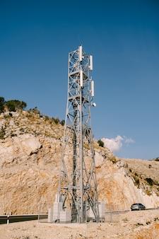 Stazione base cellulare vicino all'autostrada contro la superficie delle montagne