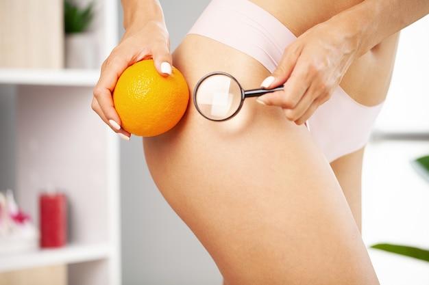 Concetto di problema della cellulite, giovane donna che tiene arancio vicino alla sua gamba.
