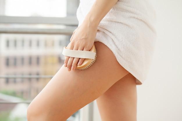 Trattamento anticellulite, braccio della donna che tiene la spazzola asciutta alla gamba.