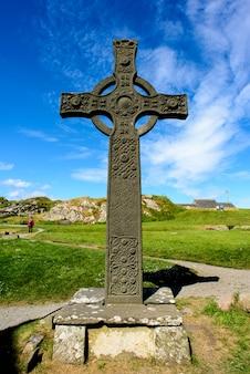 Croce celtica al giorno soleggiato nell'abbazia di iona, scozia