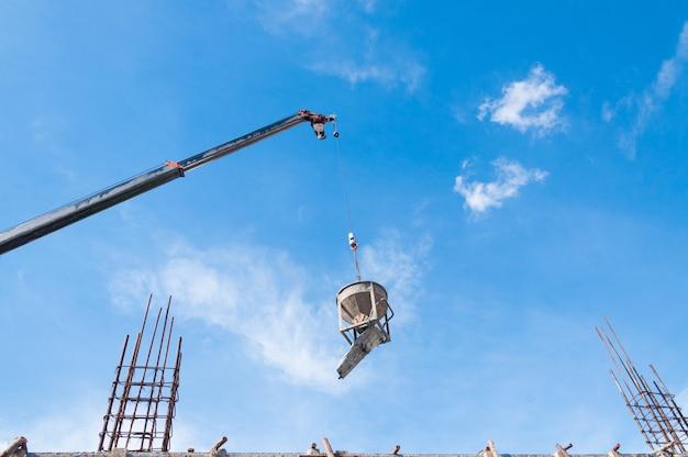 Cemento o secchio di cemento appeso al filo in cantiere con cielo blu