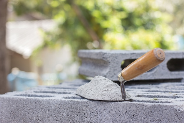Cemento in polvere con una cazzuola applicata al mattone per lavori di costruzione