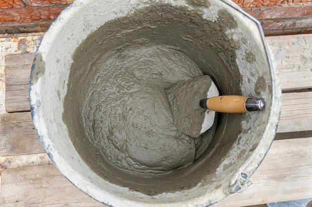 Miscela di cemento cemento-sabbia in un secchio di plastica con una spatola