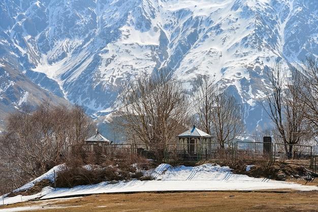 Un cimitero su una collina in una valle di montagna. sullo sfondo le alte montagne innevate.