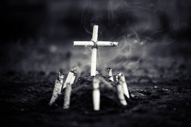 Un cimitero con una tomba fatta di sigarette. morte per danno da nicotina o fumo di tabacco da sigarette. la sigaretta uccide. foto cupa in bianco e nero.