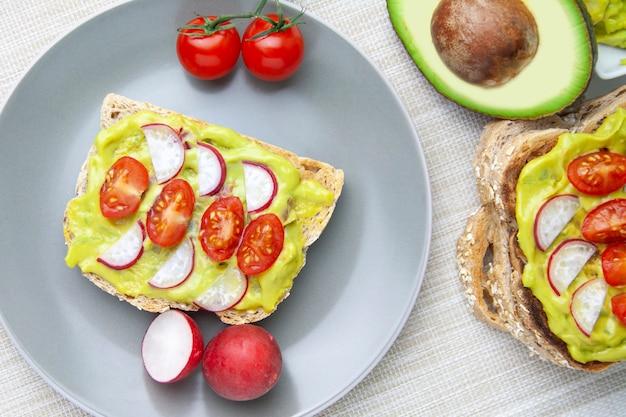 Vista cénital di pane tostato con avocado, pomodoro e ravanello su un piatto e gli ingredienti