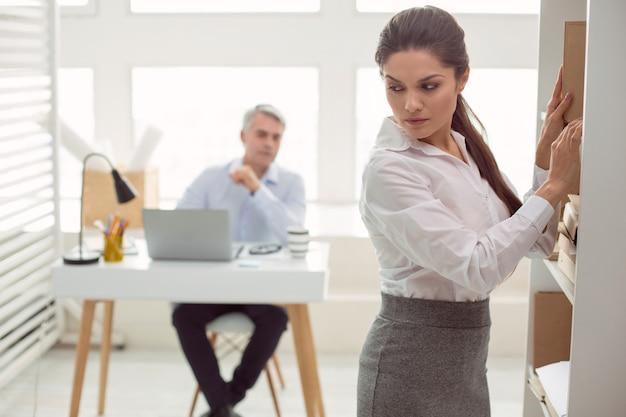 Al centro dell'attenzione. attraente e piacevole giovane donna in piedi vicino allo scaffale e girando la testa mentre viene guardata