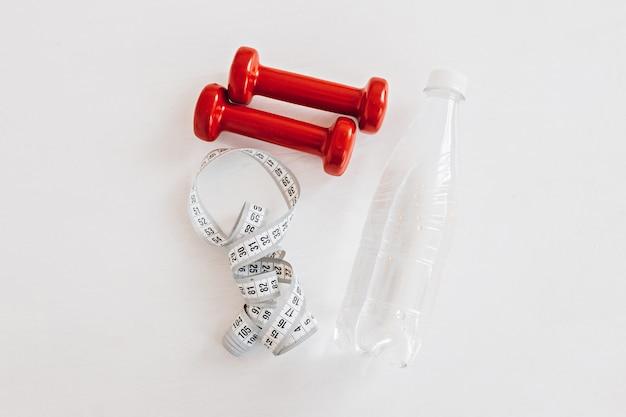 Un centimetro, una bottiglia d'acqua e manubri rossi. assistenza sanitaria, dieta e concetto di sport