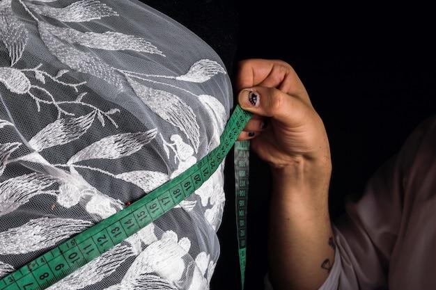 Un centimetro è uno strumento da sarto per misurare durante il cucito - primo piano delle mani di satre che prendono le misure.